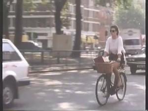 Woman cycling around Shepherds Bush Green - lovely practical bike!